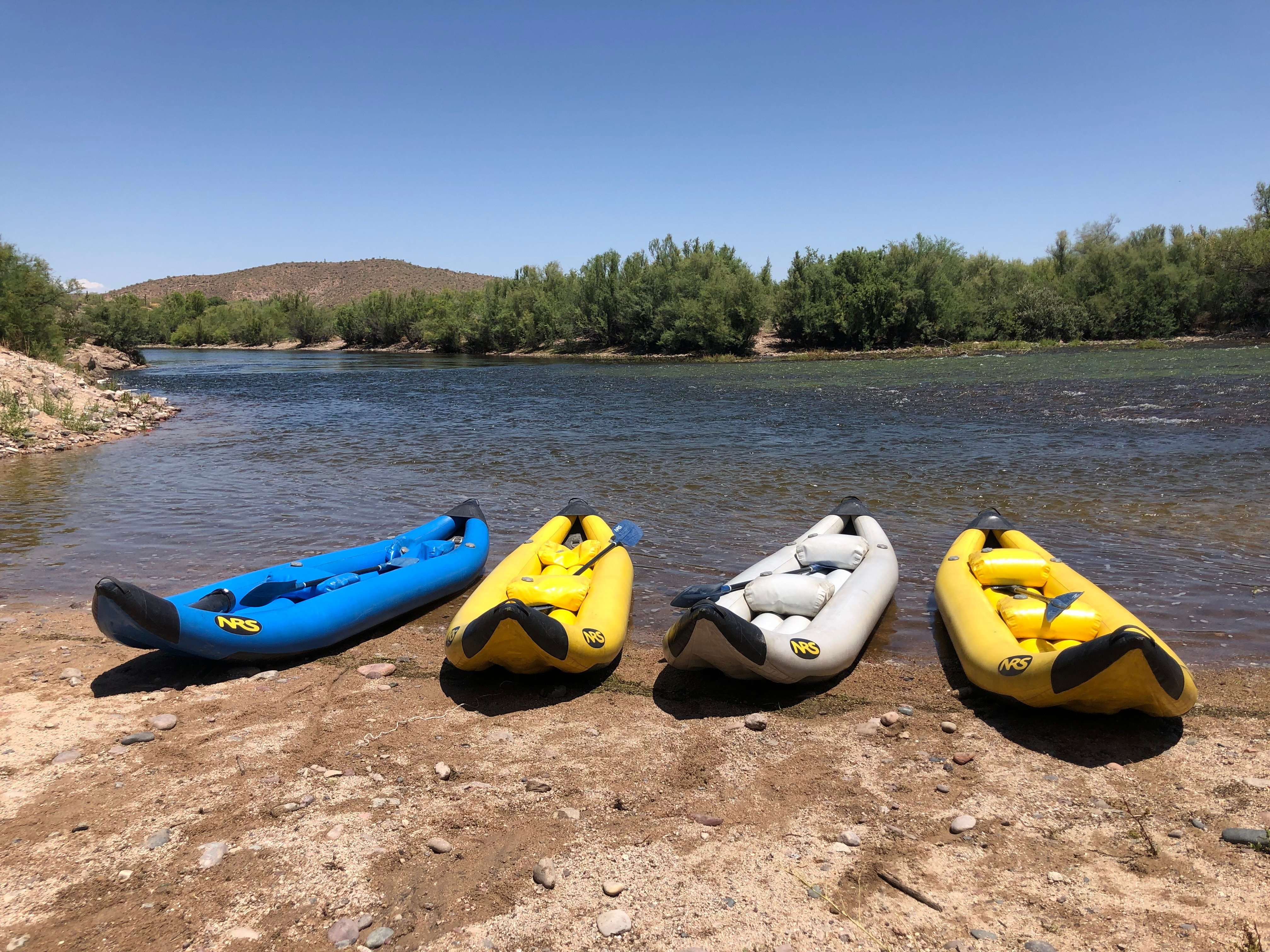 Multi colored kayaks rest on the banks of a river. - Kayaking gear essentials