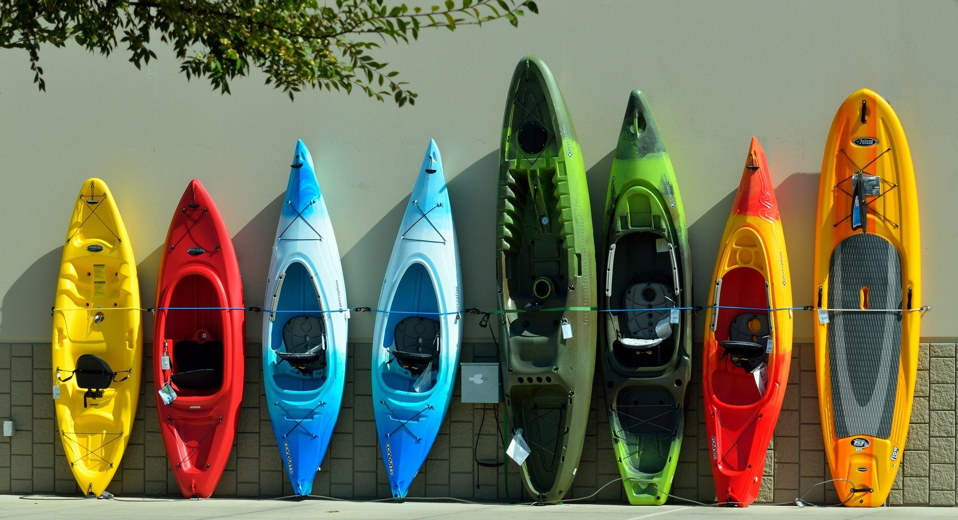 Colorful kayaks leaning against a wall.