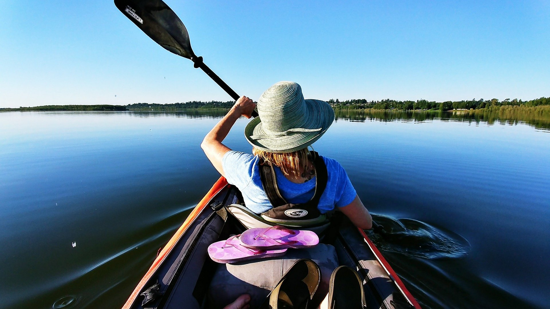 Woman kayaking on a still lake with a hat on.