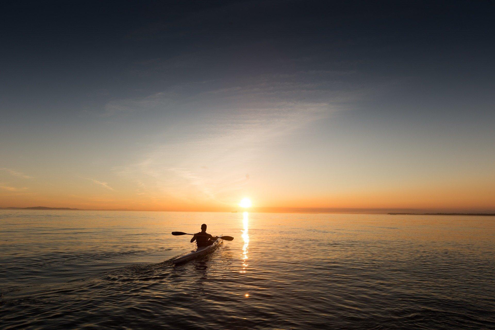 A man kayaks into the sunset.