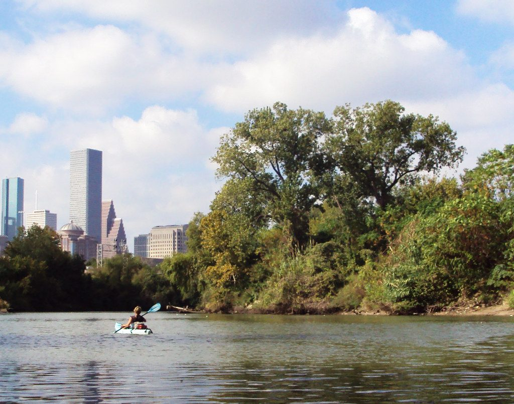 Kayaking in Houston (Buffalo Bayou) with the city skyline in the background.