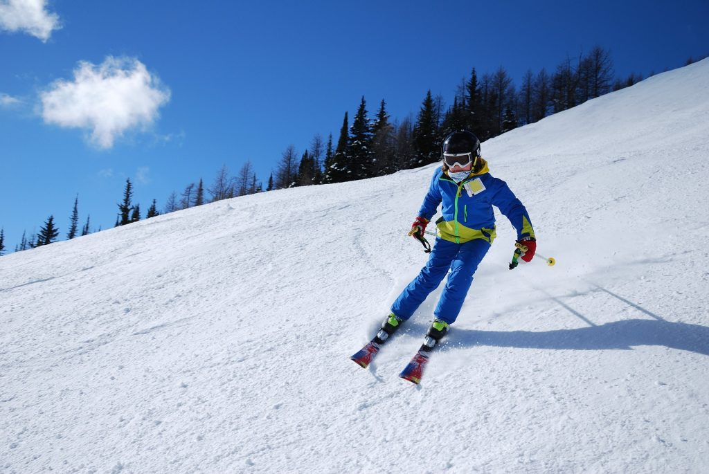 A woman skis down a snowy slope. Creative commons image as part of our ski trip packing list guide.