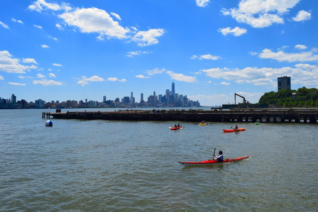 Kayakers surround New York City's harbors with the New York City skyline on the horizon.