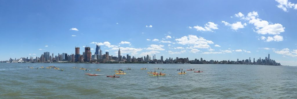 A panoramic view  of kayaking in New York City with the picturesque skyline on the horizon.