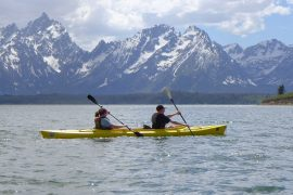 Kayakers paddle in front of snow-capped mountains around Grand Lake.