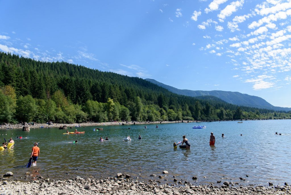 Kayakers and Tubers float near the rocky shores of Rattlesnake Lake in Seattle