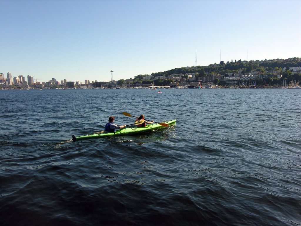 Seattle's skyline is in the distance as kayakers paddle towards the pine tree-lined coast