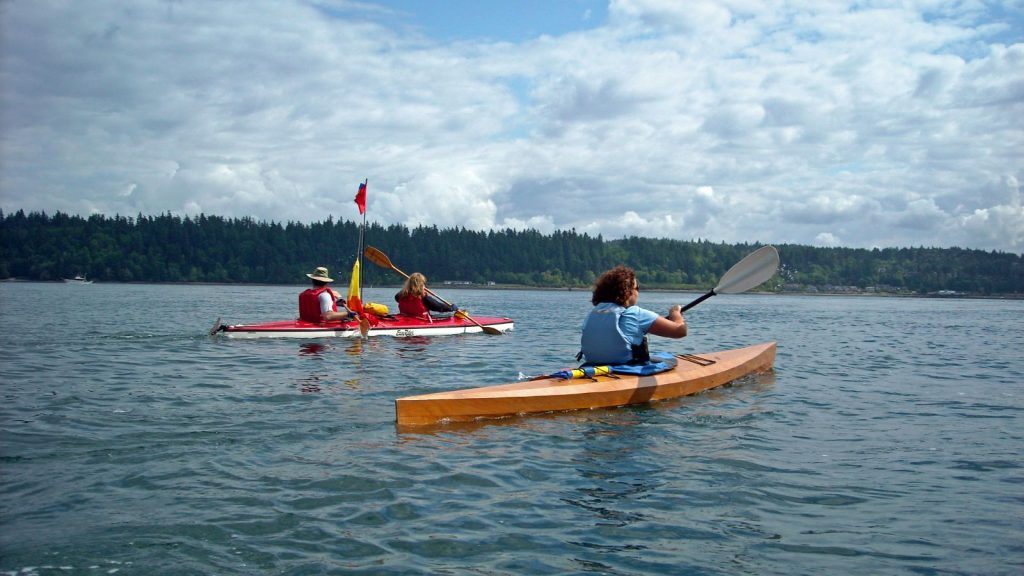 Orange kayaks slice through the water while paddling to Blake Island's tree-lined coast
