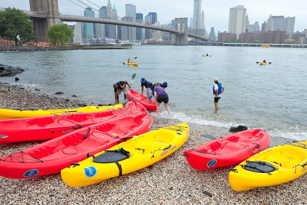 Red and yellow kayaks sit on the rocky shore beneath the Brooklyn Bridge, a very convenient launch spot for kayaking in New York City.