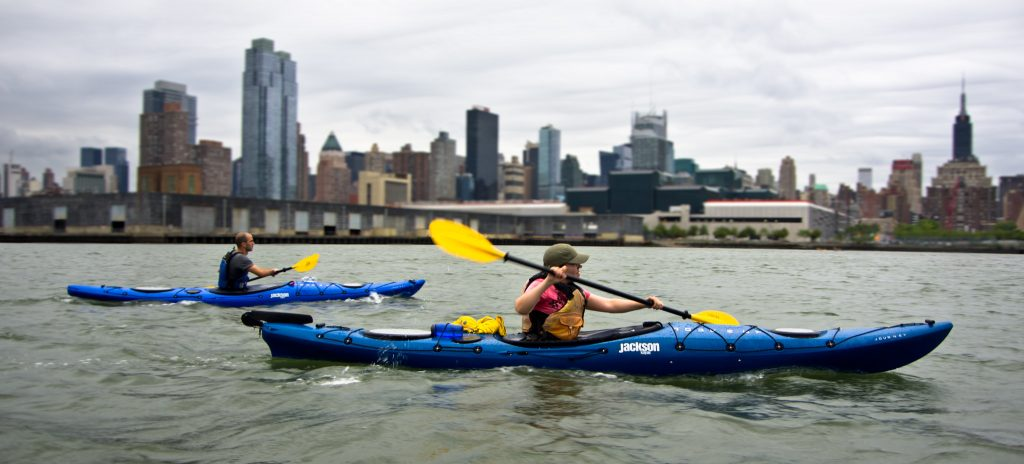 Two blue kayaks rush through the water with the New York skyline behind them in the distance.