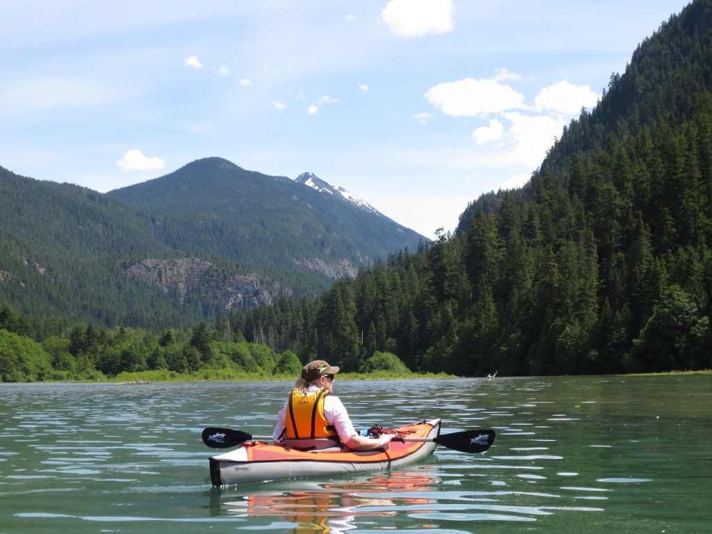 A single kayaker marvels at the gigantic mountains and trees of Pyramid Lake in Los Angeles.