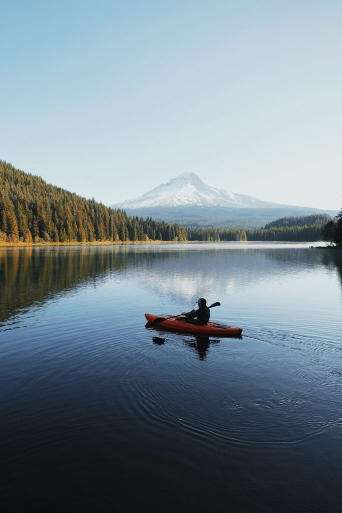 A single kayak approaches the sandy shores of Seattle's coastline with smooth, clear waters all around.