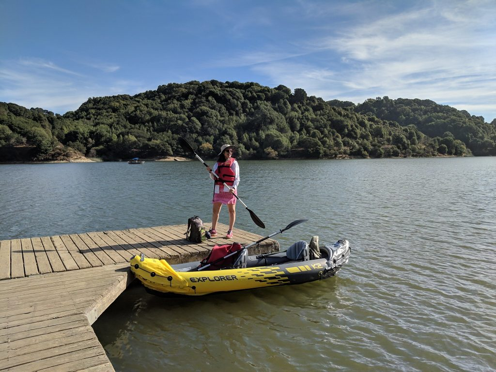 A kayaker gets ready to paddle around Lake  Chabot in San Francisco. Blue waters surround densely forested mini islands.