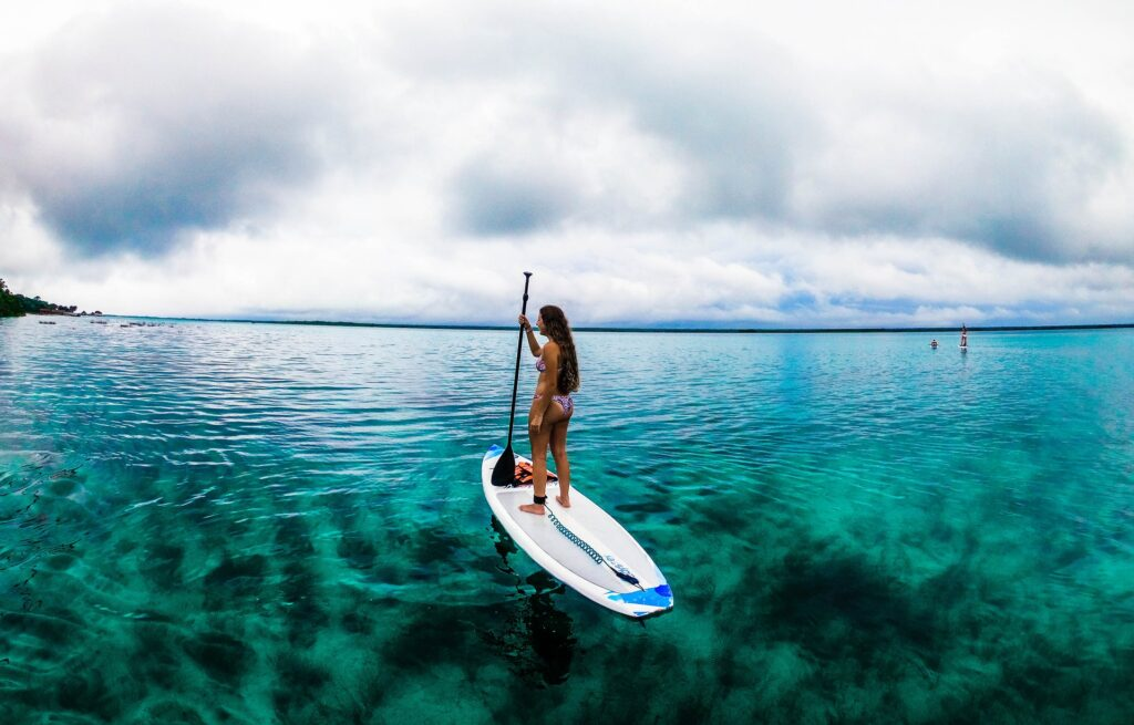 A woman standing on a paddle board enjoys the wide-open waters and beautiful views around her.