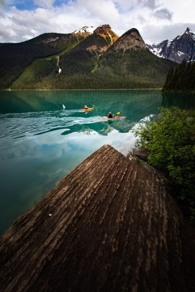 a group  of kayakers start on a long yet epic kayak journey beside mountains.
