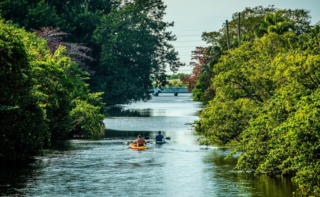 two kayakers enjoy a scenic route down a river and remind themselves of inspirational canoe and kayaking quotes that motivated them to take this journey.
