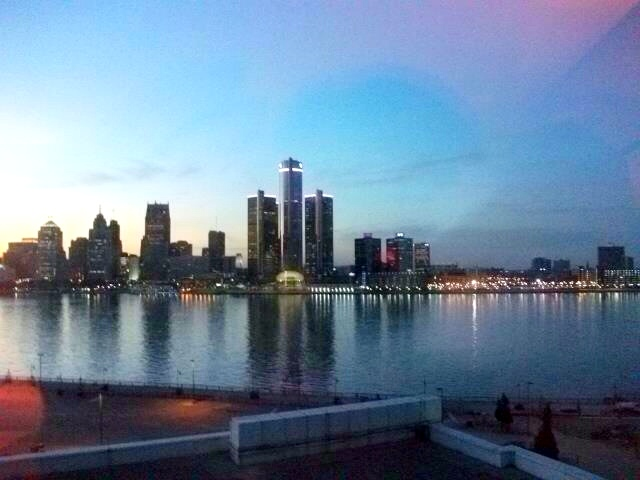 The Detroit skyline is lit up at night with water in front. This is a great place to go kayaking.