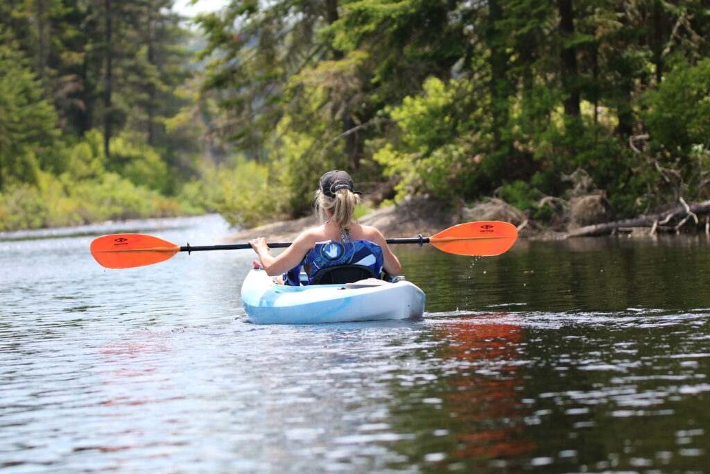 a kayaker enjoys ging kayaking  in Minneapolis and the Twin Cities. There are clear waters and pine trees.