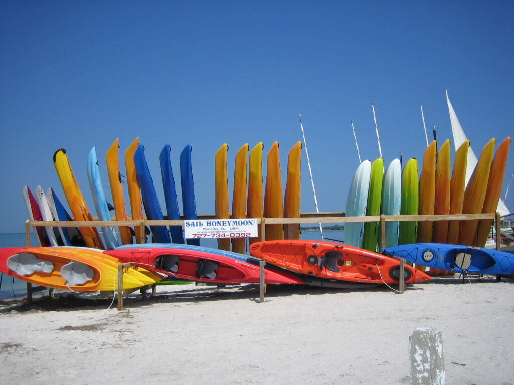 colorful kayaks line the beach where people enjoy kayaking in Tampa