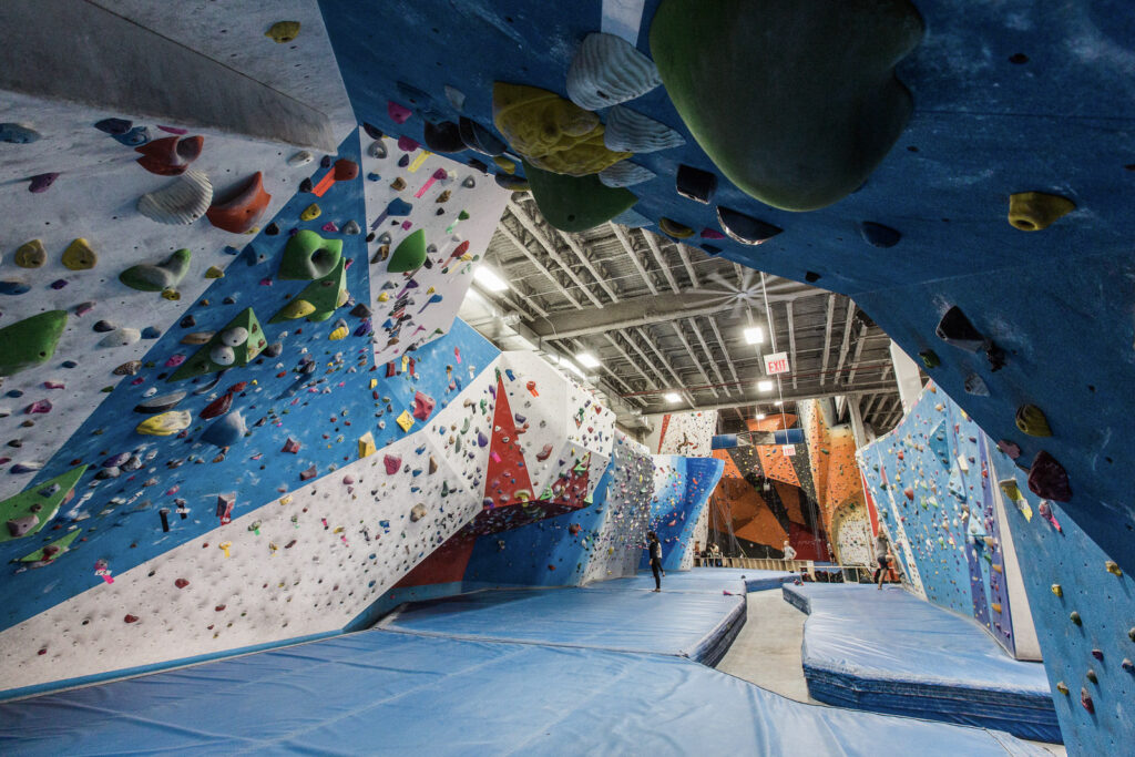 The Cliffs at LIC rock climbing gym in NYC in New York City, showing off their bouldering, with strategically placed top ropes in the background.