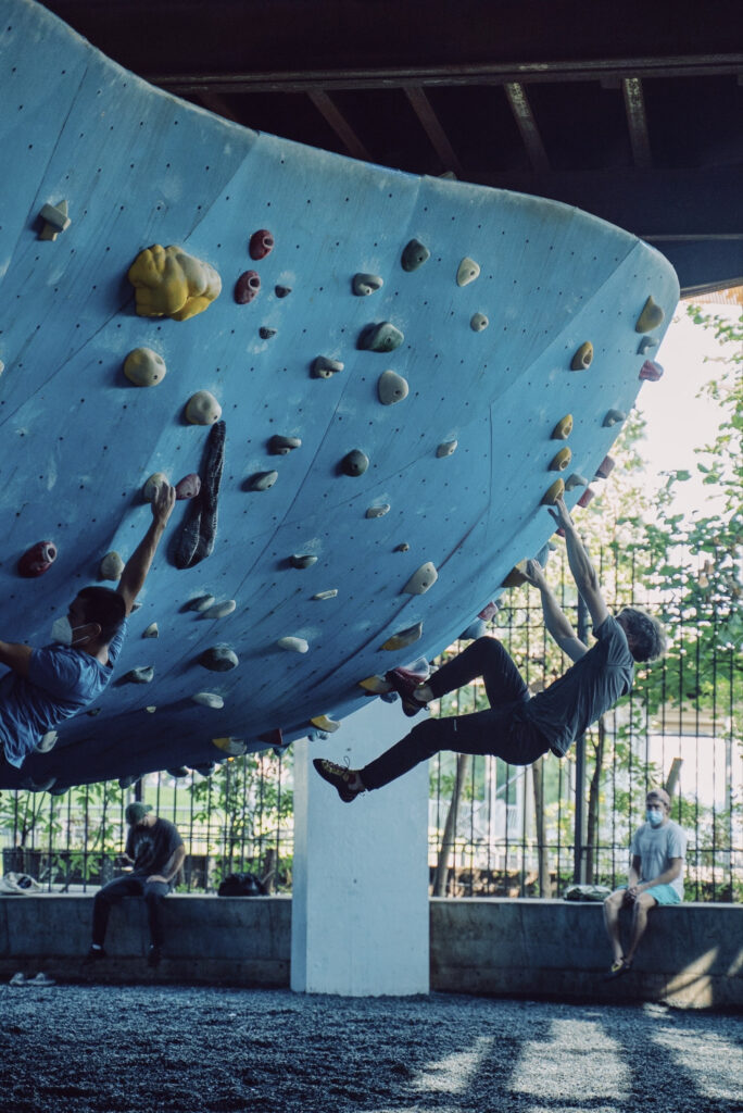 This rock climbing wall in NYC is outdoors and features a cool sloping overhang that starts steep and eases off the further round you climb, but I'm sure the hold size will be decrasing accordingly.