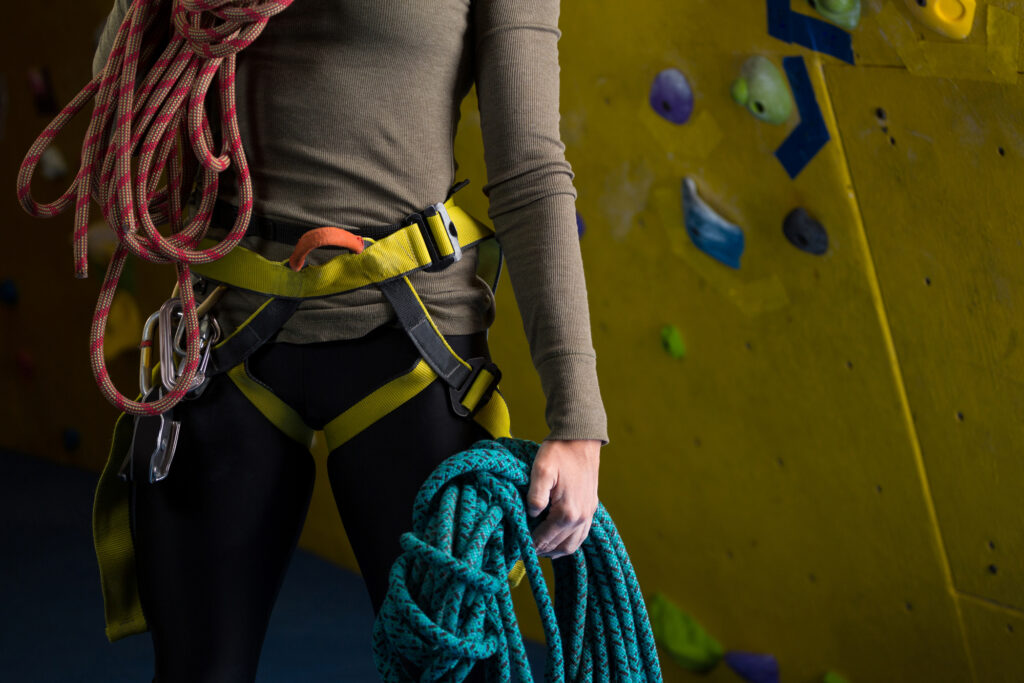 Woman wearing a rental harness holding multiple ropes