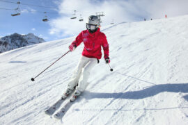Best women's ski jackets: woman skiing in red jacket with chairlift in the background