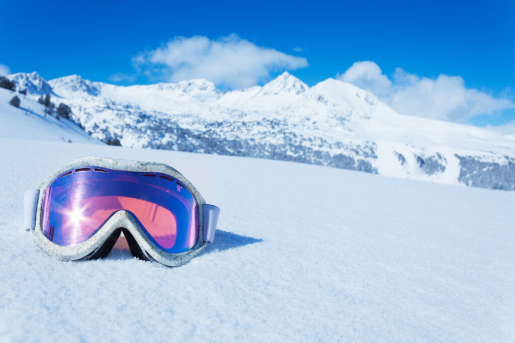 A ski mask is an essential item for what to wear skiing - pink ski goggles on snow slope.