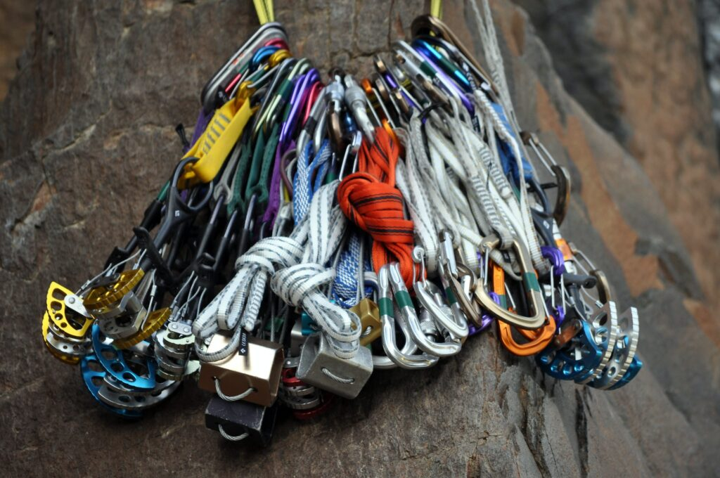Full rack of trad climbing equipment including rocks, cams, quickdraws, slings and hexes