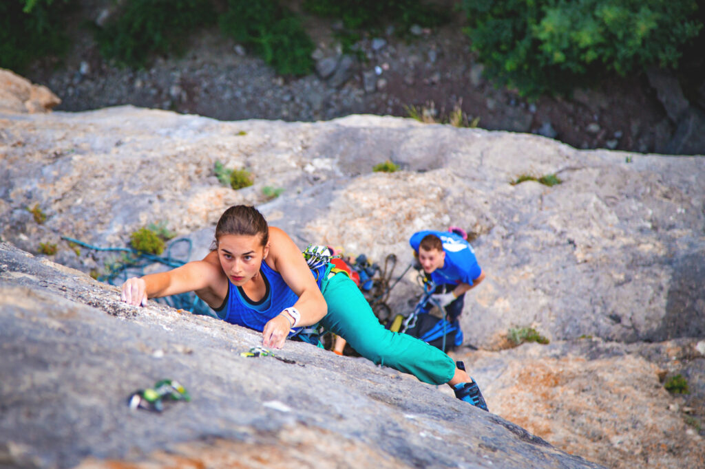 Woman Lead Climbing with her essential essential sport rock climbing gear