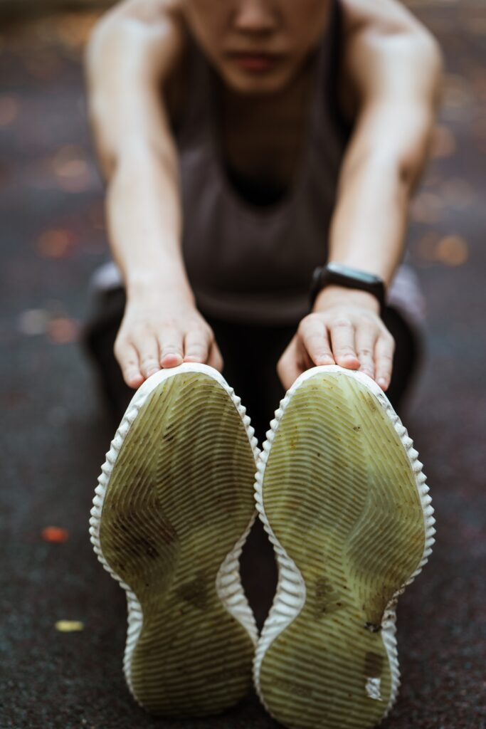 a women stretches to reach her shoes