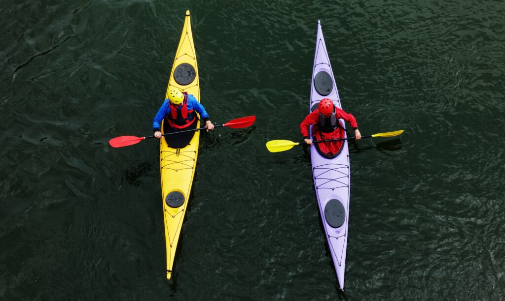 two types of kayaks in the ocean, bright colors