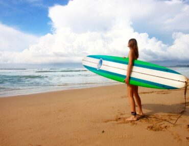 A female surfer looks off into the distance holding a green longboard and thinking about all of the best gifts for surfers.