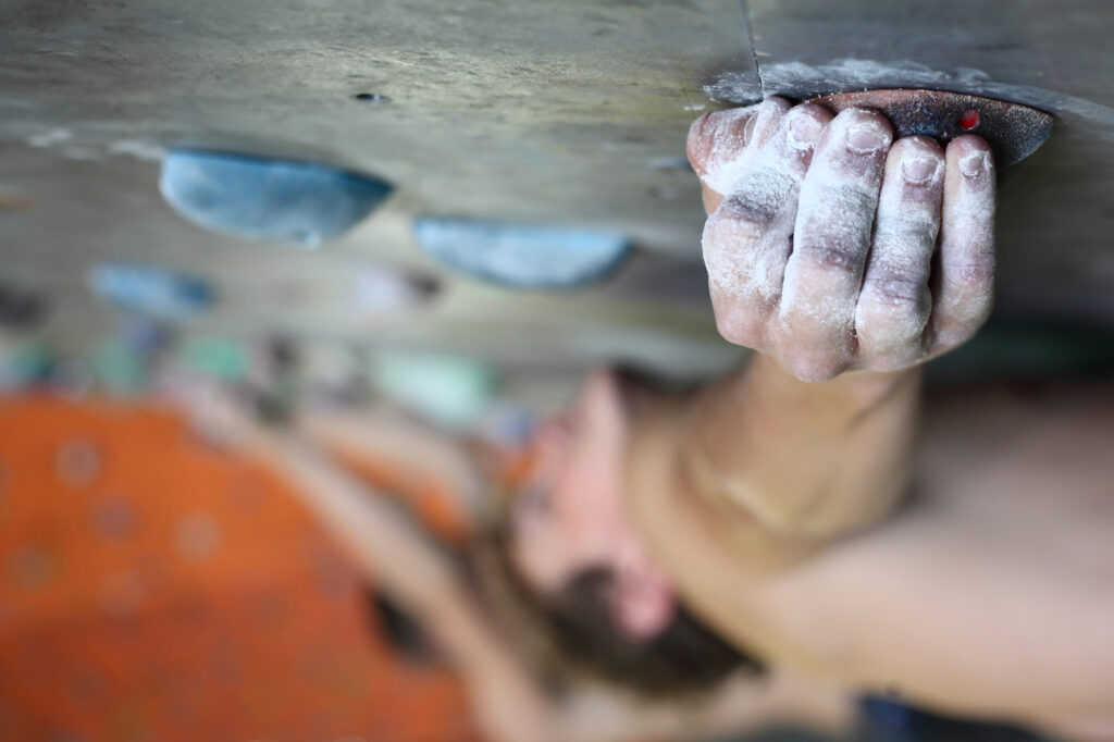 Rock climber crimping on resin hold